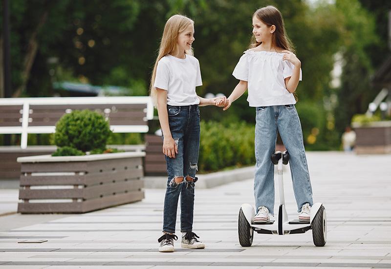 Los niños aprenden a montar hoverboard en un parque en el soleado día de verano (2)