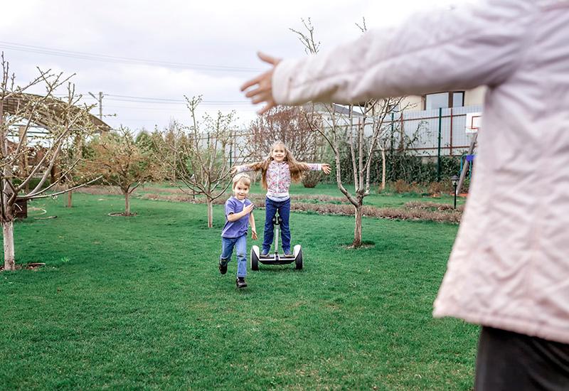 Niño montando en el tablero de auto-equilibrio en el patio trasero de la casa de campo