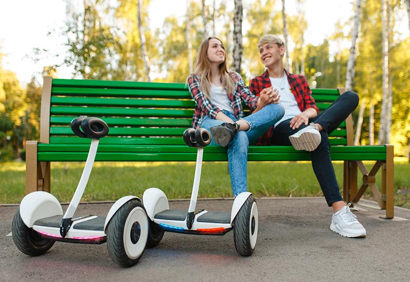 Pareja con giroboard sentado en el banco en Parque