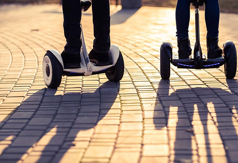 Piernas masculinas en scooter eléctrico al aire libre giroscopio