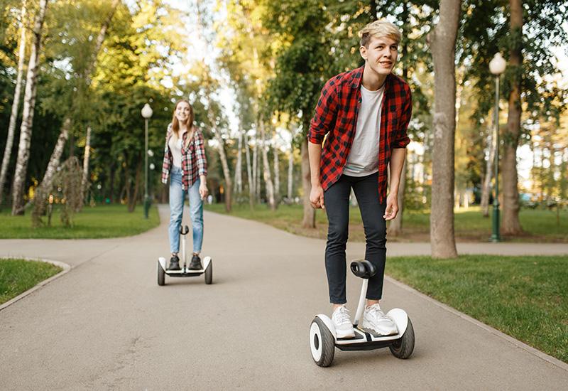 jóvenes pareja a caballo en giroscopio tablas en verano Parque